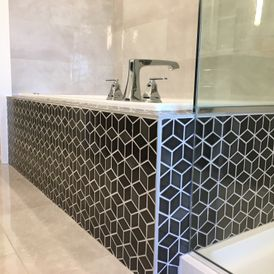 stone bath room with black tile flooring
