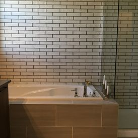 stone bath tub with grey tile flooring