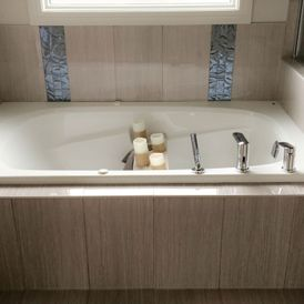 bath tub with brown stone flooring